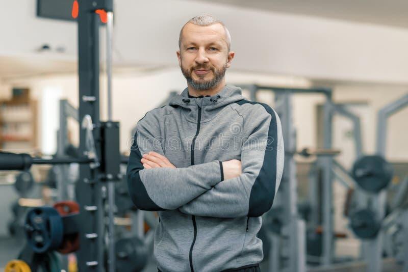 运动的人画象用在健身房,看照相机的英俊的有胡子的教练员的被折叠的手 库存照片
