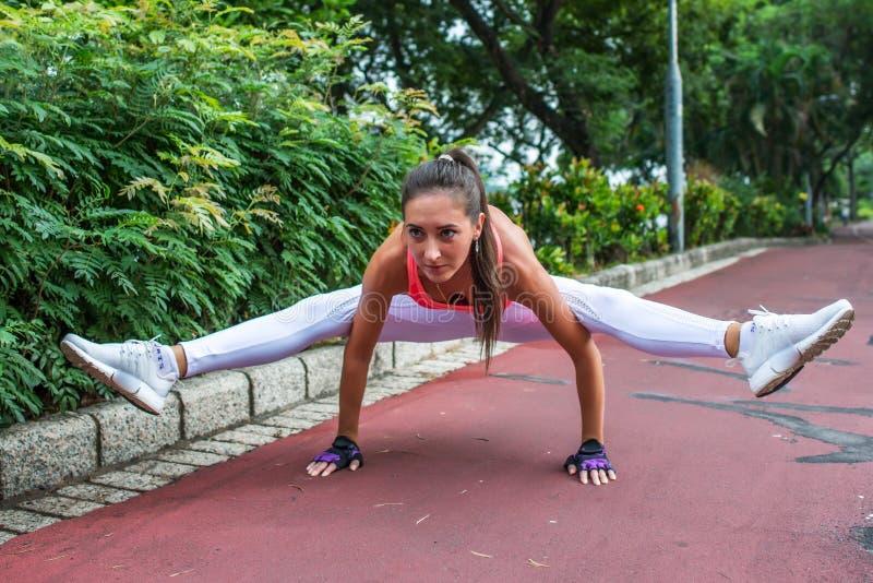 运动的做在萤火虫姿势的适合少妇手倒立锻炼 解决在公园的女运动员 库存照片