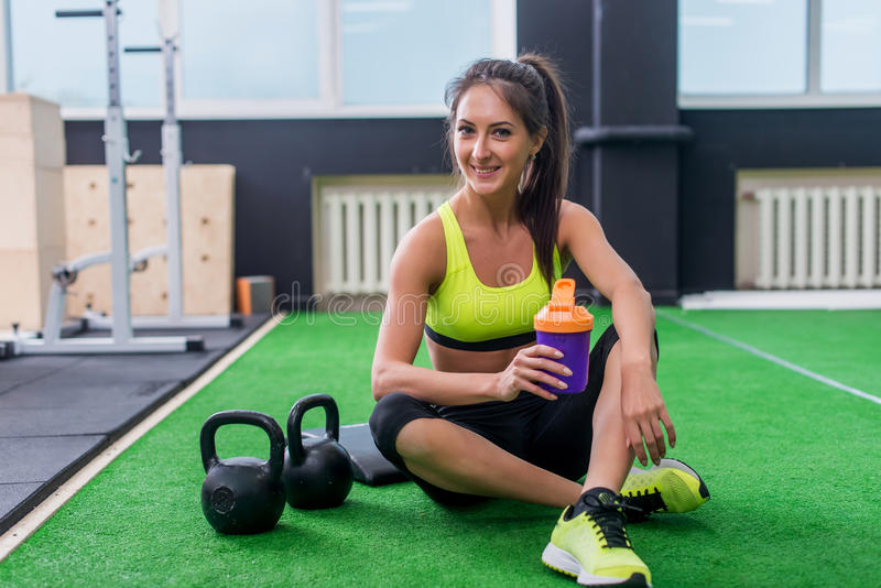 年轻运动的在健身房的妇女饮用水,拿着瓶,有断裂 库存照片