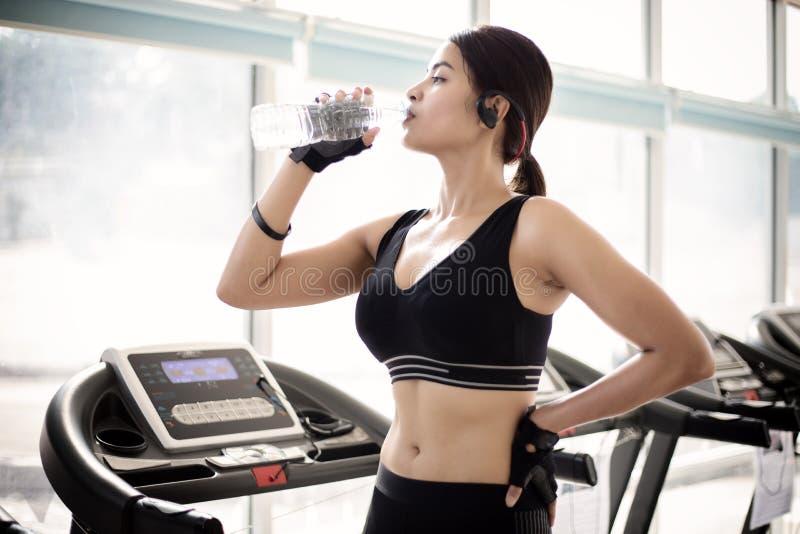 运动的在锻炼以后的妇女亚洲饮用水在健身房 Fi 免版税库存图片