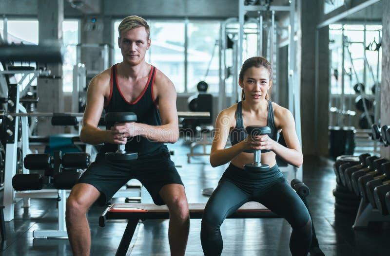 运动的夫妇男人和妇女行使与哑铃或做锻炼在健身房 免版税库存图片