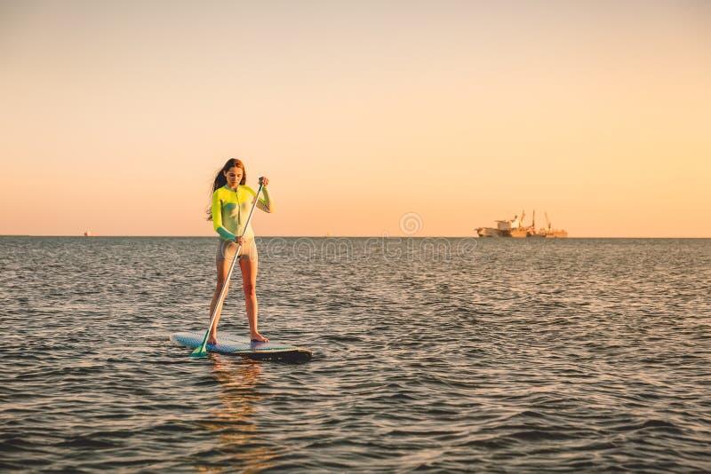 运动的女孩站立冲浪与美好的日落颜色的桨 免版税库存照片