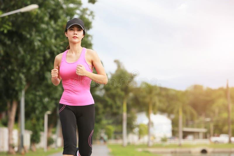 运动的女性慢跑者早晨锻炼在公园 免版税库存照片