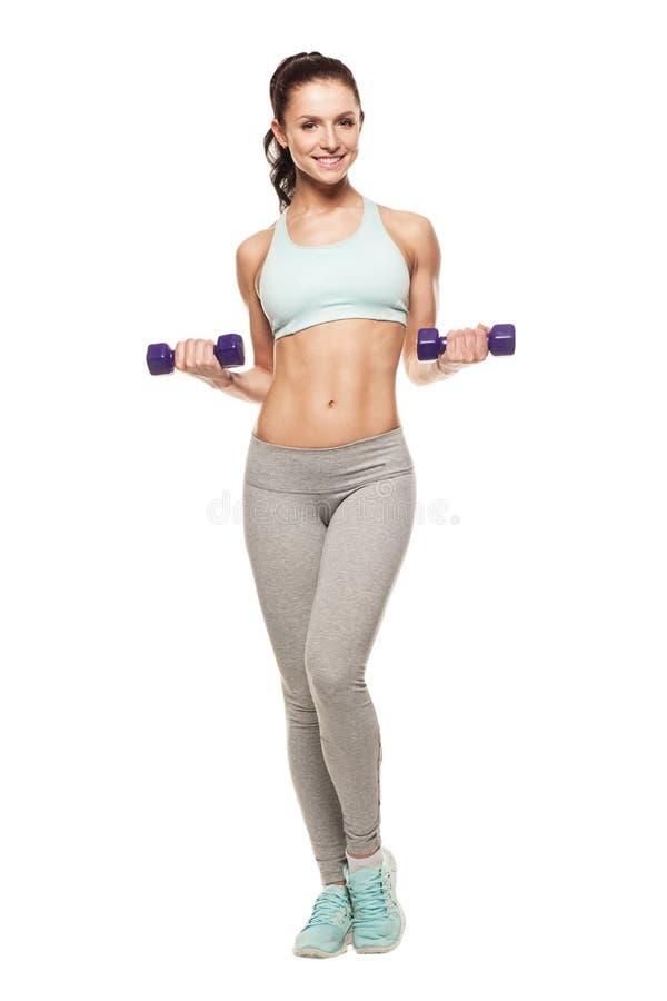 运动的妇女做她的与哑铃的锻炼 免版税图库摄影