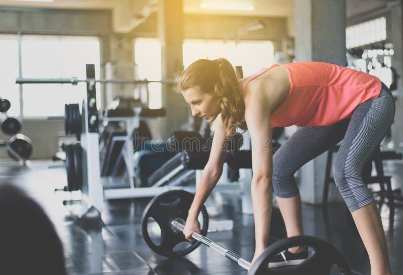 运动的妇女行使与杠铃,女性做行使在健身房 库存图片