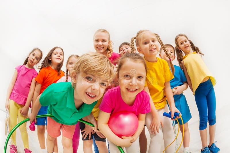 运动的孩子和体操教练获得乐趣在健身房 免版税库存图片