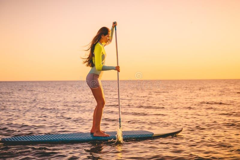 运动的少妇在站立有美好的日落颜色的明轮轮叶 免版税图库摄影