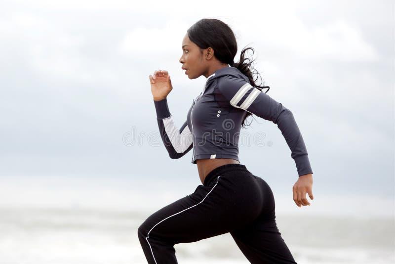 运动的年轻黑人妇女赛跑 库存照片