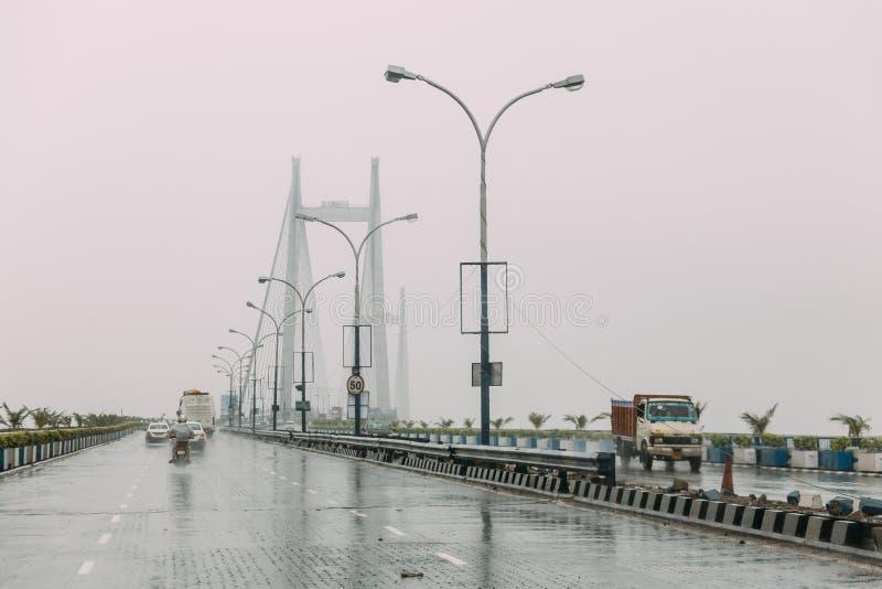 运动的汽车,当下雨在Vidyasagar Setu桥梁,钢结构与雨的下午在加尔各答,印度时 免版税图库摄影