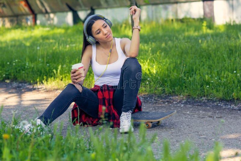 运动的溜冰板者女孩坐滑板饮料咖啡和听的音乐 免版税图库摄影