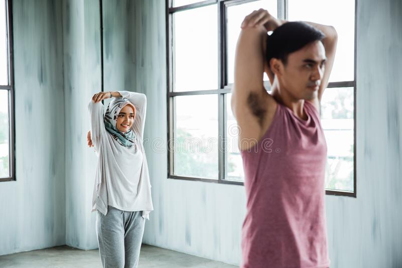 运动的男人和做舒展在核心锻炼前的hijab妇女 免版税图库摄影