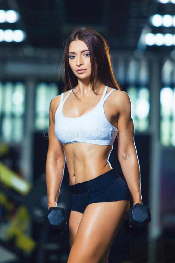 运动的短裤和顶面举行的哑铃的年轻适合的妇女,当站立在健身房时 图库摄影