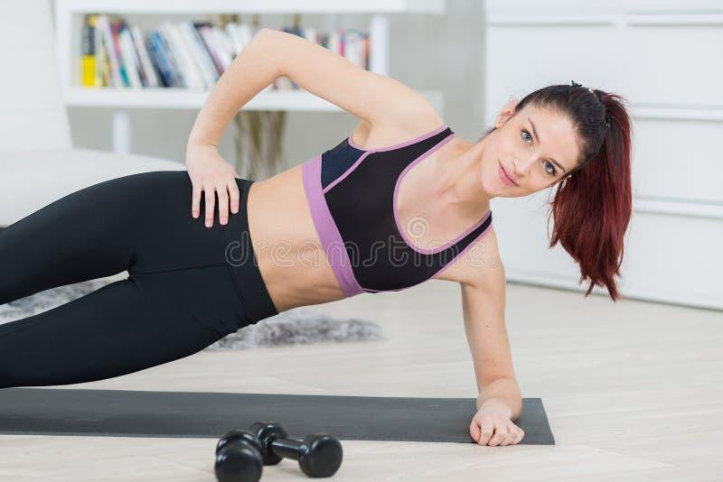 运动的美丽的年轻女人实践的瑜伽在家 免版税图库摄影