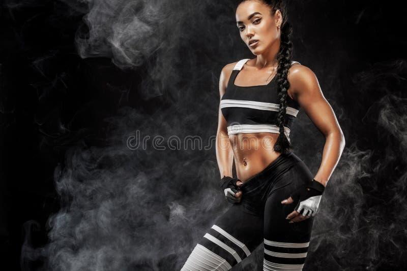 运动的美好的美国黑人的模型, sportwear的妇女做健身行使在黑背景的停留适合 库存照片
