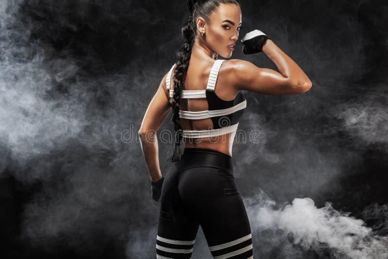 运动的美好的美国黑人的模型, sportwear的妇女做健身行使在黑背景的停留适合 免版税图库摄影