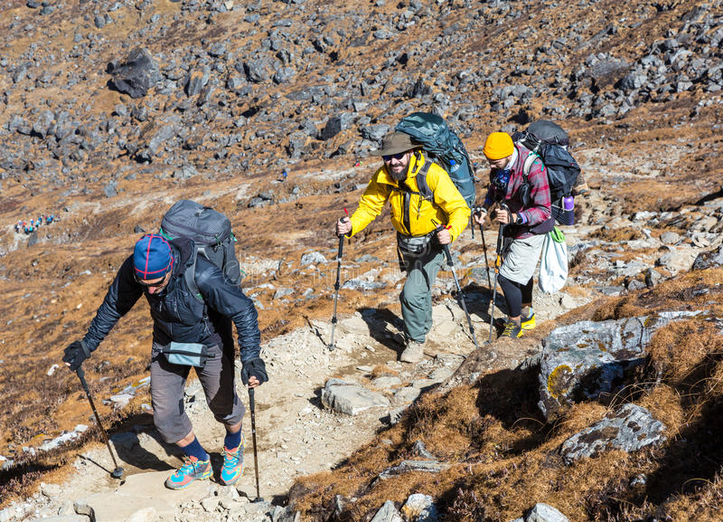 运动的衣物的走在山行迹的人 免版税库存照片