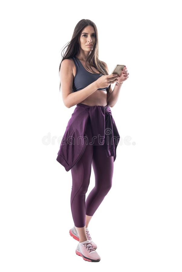 运动的衣裳的确信的年轻有氧运动辅导员使用看照相机的手机 免版税库存照片