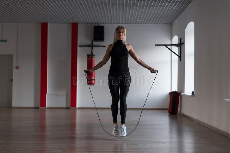 运动的黑绑腿的年轻女人在时髦的运动鞋做在健身房的跳绳 女孩向体育求助在健身演播室 库存照片
