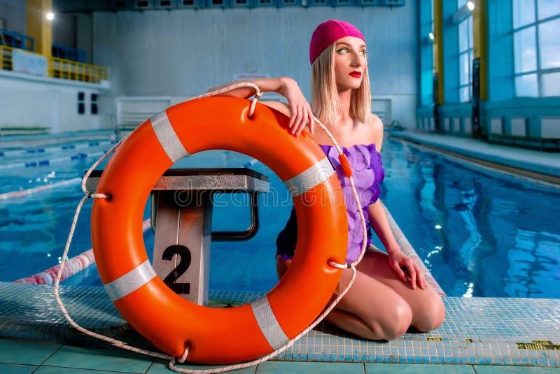 运动美丽的可爱的白肤金发的妇女救生员画象有时髦的在游泳盖帽和游泳衣组成 免版税库存照片