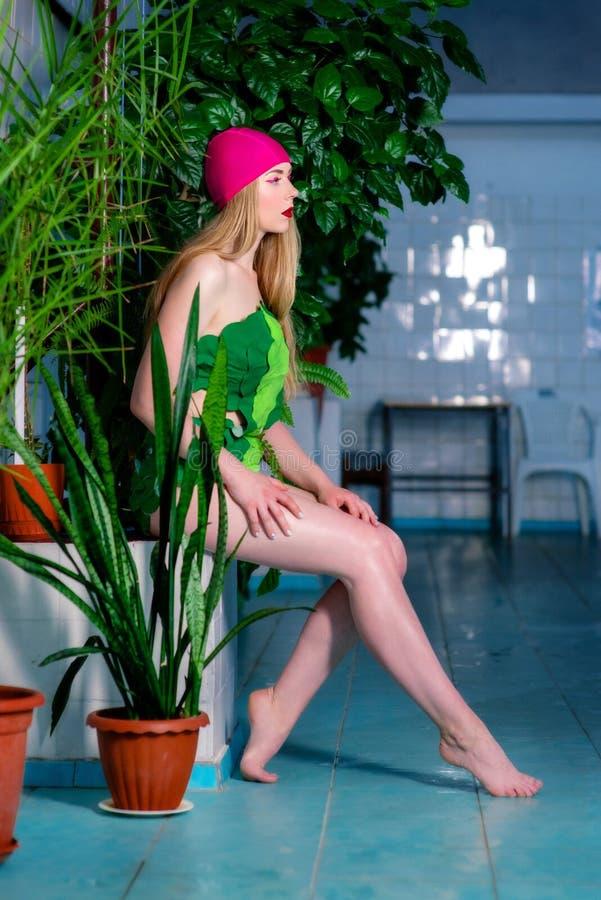 运动美丽的可爱的白肤金发的妇女画象与在游泳盖帽和衣服组成在游泳池 免版税库存照片
