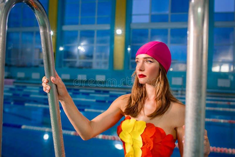 运动美丽的可爱的白肤金发的妇女画象有时髦的在桃红色游泳盖帽和游泳衣组成 免版税库存图片