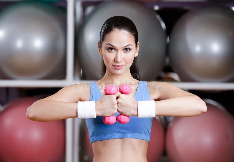 运动装培训的少妇与哑铃 免版税库存图片
