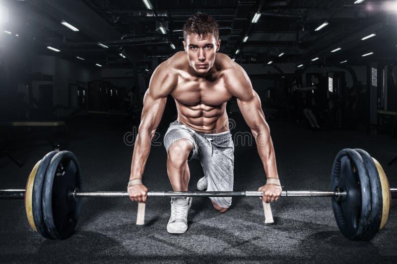 运动赤裸上身的年轻体育人-健身模型拿着在健身房的杠铃 复制空间前面您的文本 图库摄影