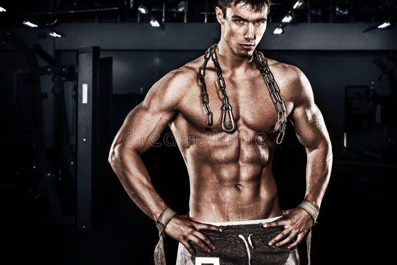 运动赤裸上身的年轻体育人-健身模型拿着在健身房的链子 复制空间前面您的文本 免版税库存图片