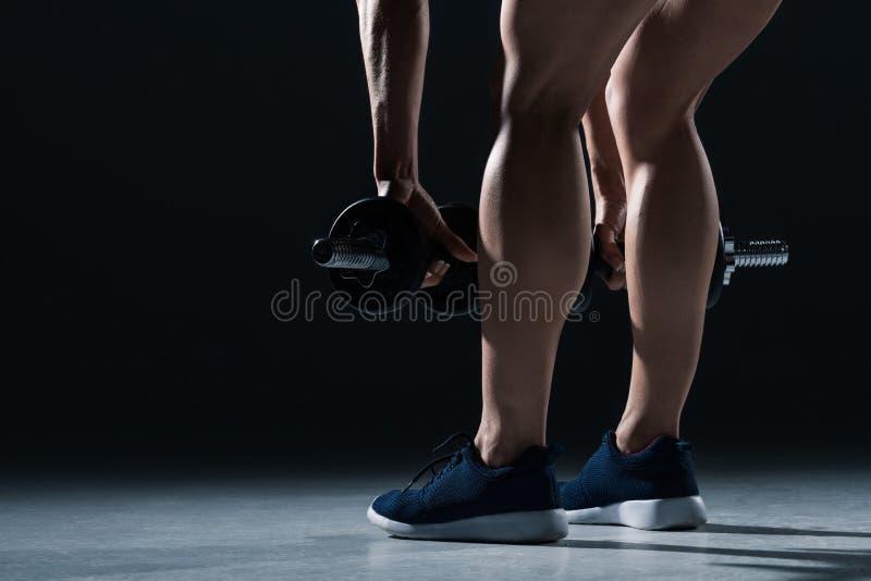 运动鞋的女性爱好健美者训练与哑铃的低部分观点的, 免版税库存图片