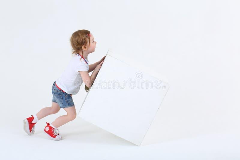 运动鞋的小逗人喜爱的女孩推挤大白色立方体 免版税图库摄影
