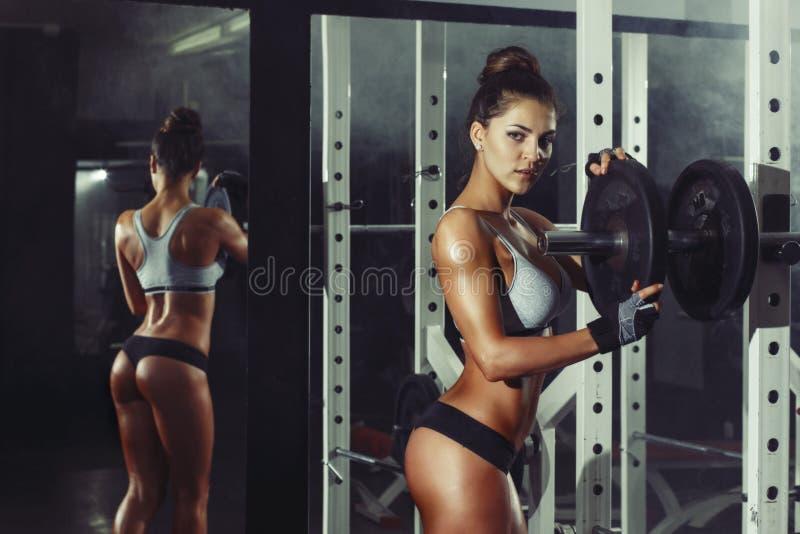 运动年轻性感的女孩设置在杠铃的重量在健身房 免版税库存照片