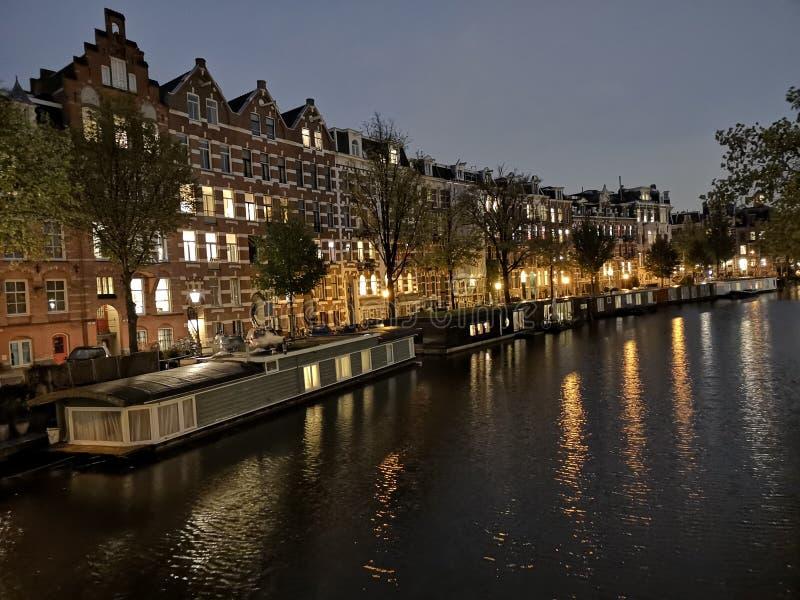 运河、桥梁、阿姆斯特丹市自行车和房子,在荷兰,荷兰在晚上 免版税库存照片