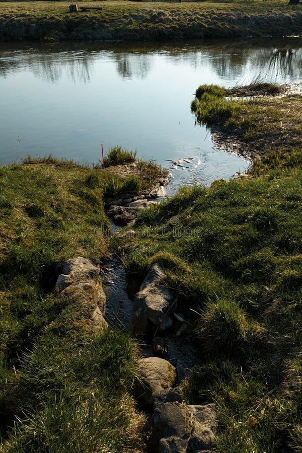 运河在城市萨比莱,拉脱维亚加入一条河 库存照片