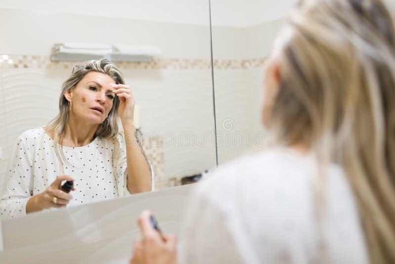 运用早晨的妇女组成在卫生间的镜子 免版税库存照片
