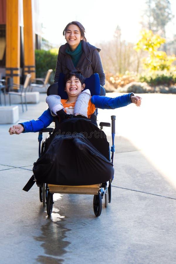 运行与照料者的轮椅的残疾男孩户外 免版税库存图片