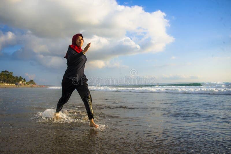 运行和跑步在海滩的回教hijab顶头围巾的年轻健康和活跃赛跑者回教妇女佩带传统阿拉伯人 免版税库存照片