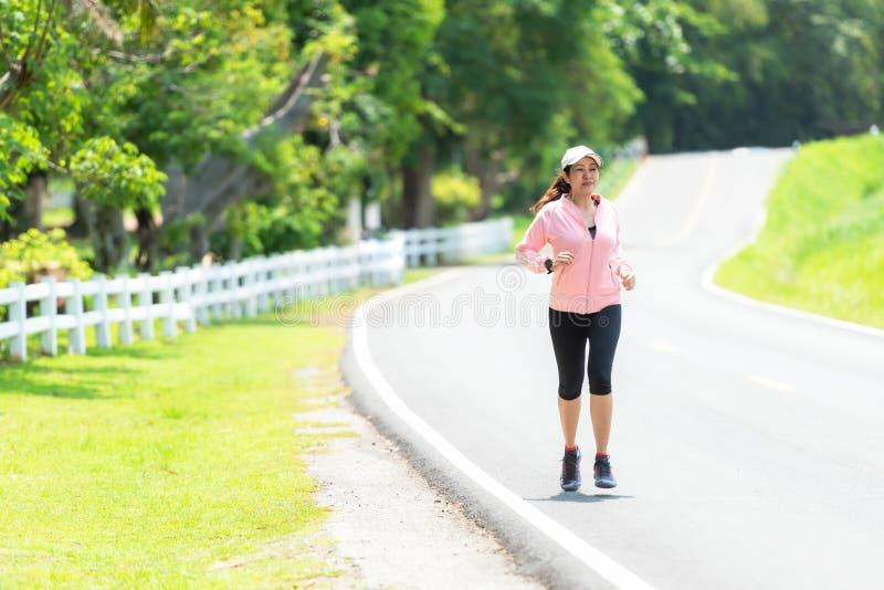 运行和跑步通过路的运动的亚洲妇女赛跑者 免版税库存照片