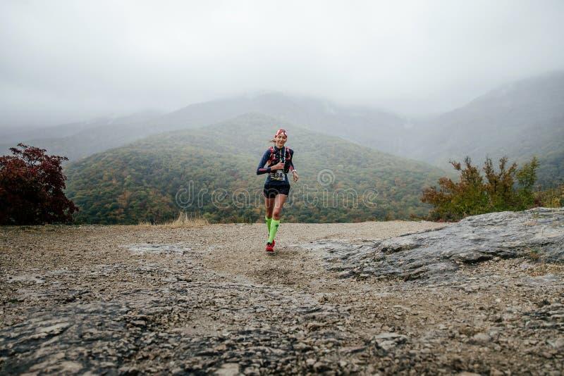 运行在与微笑的雨中的女孩赛跑者在面孔 免版税图库摄影