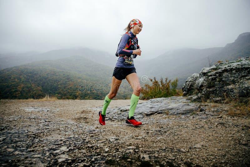 运行在压缩袜子和连续背包的雨中的女孩赛跑者 图库摄影