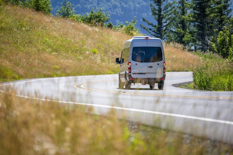 运行在有小山的弯曲道路的商业紧凑微型搬运车在边 免版税图库摄影