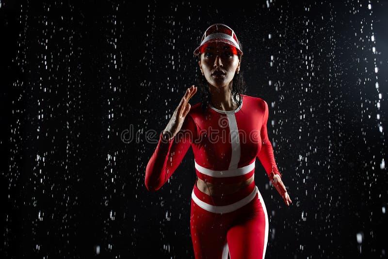 运行在水色演播室的运动服的美丽的少女 水滴被传播关于她的健身身体 免版税图库摄影