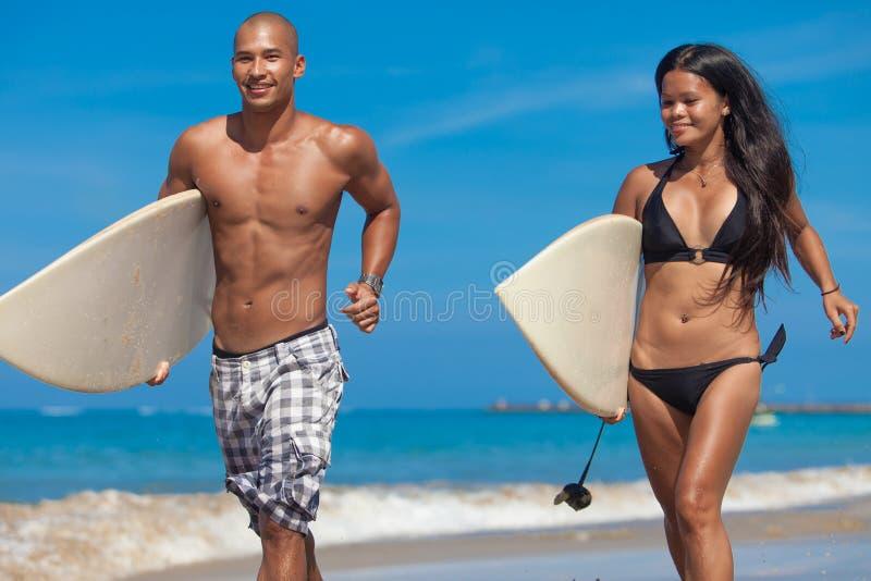 运行在海滩的新夫妇 免版税库存照片