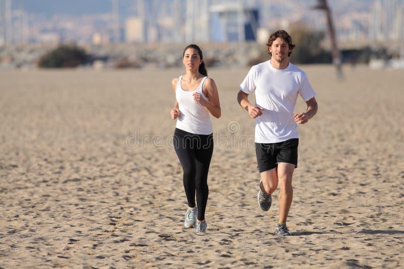运行在海滩的男人和妇女 图库摄影