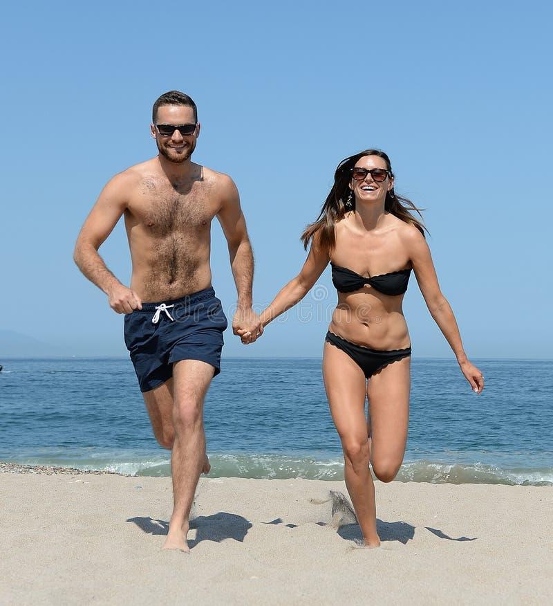 运行在海滩的夫妇 免版税图库摄影