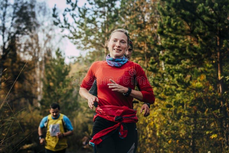 运行在秋天公园的年轻微笑的女孩赛跑者 库存图片