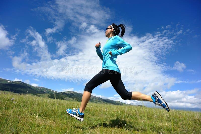 运行在美丽的足迹的年轻健身妇女赛跑者在草原 免版税库存照片