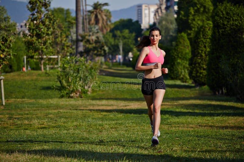 运行在美好的树背景的公园的明亮的运动服的年轻运动的女孩 免版税库存图片