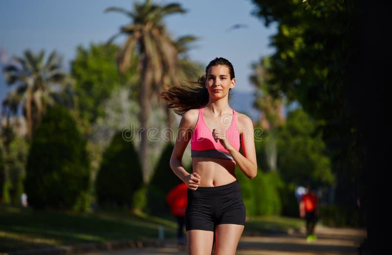 运行在美好的棕榈背景的公园的明亮的运动服的可爱的少妇 免版税库存照片