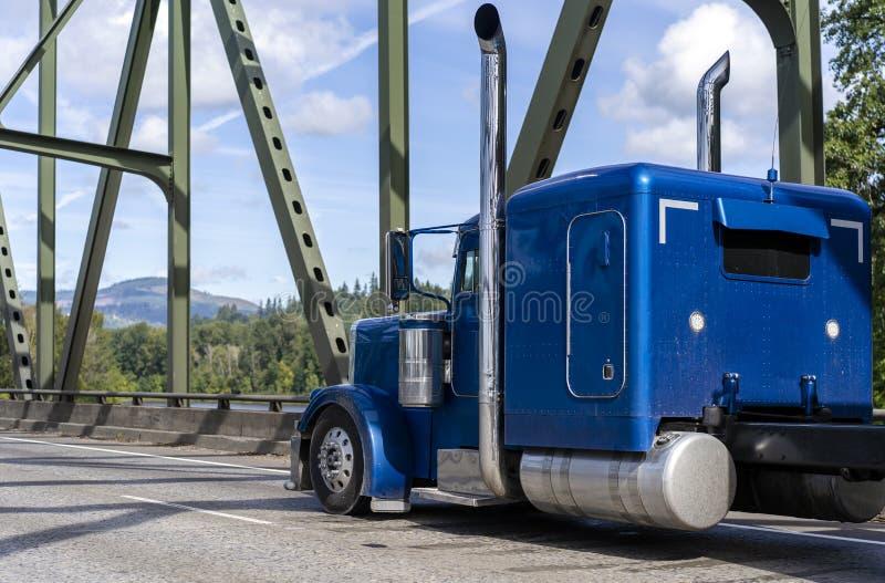 运行在被成拱形的桁架桥的明亮的蓝色经典美国偶象大半船具帽子卡车拖拉机在好日子 库存照片
