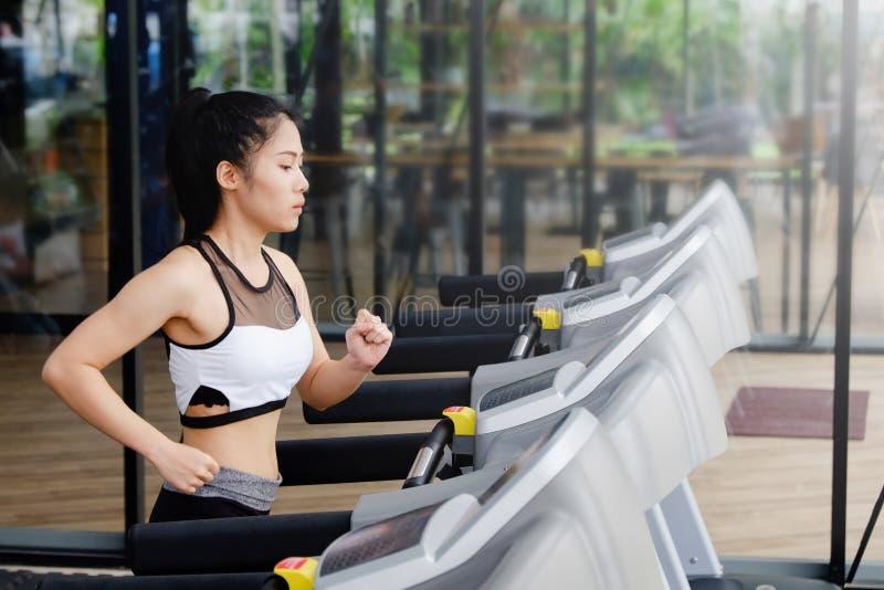 运行在踏车的运动服的妇女在健身房, cadio概念 库存照片